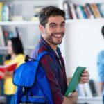 Estudiante con mochila y libro sonriendo a cámara