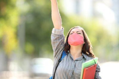 Chica estudiante con mascarilla y levantando el brazo feliz
